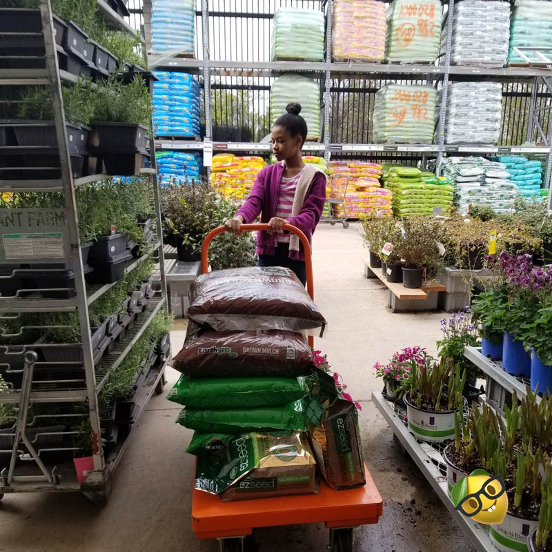 girl with a cart shopping for plants at gardening supply
