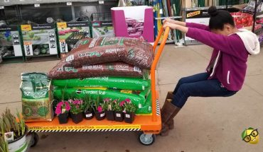 Girl pulling a cart with gardening supplies