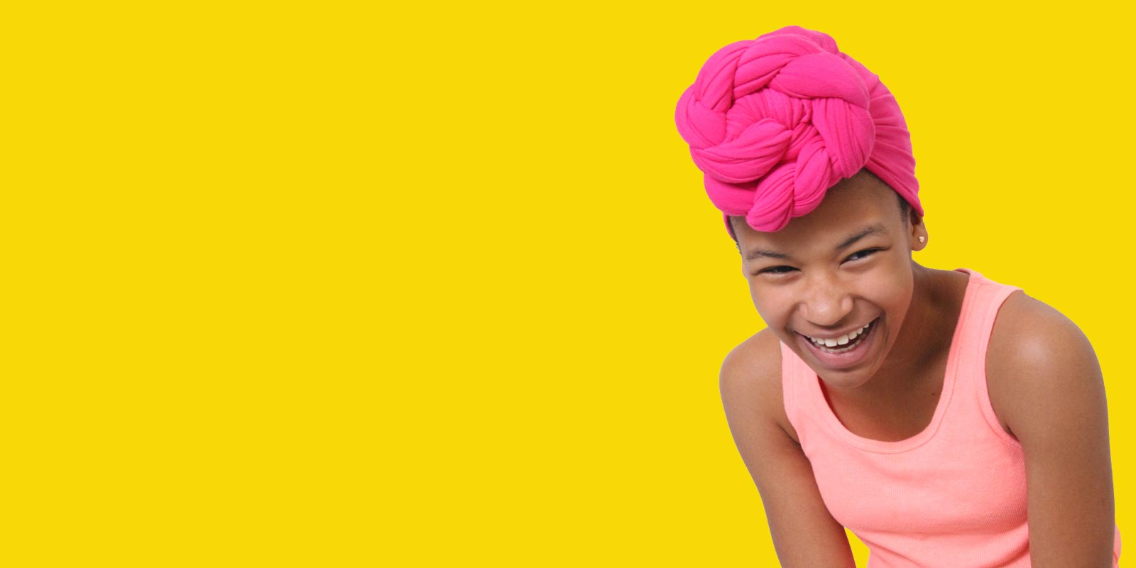 image of Eden Wilson in a pink headwrap and peach top laughing
