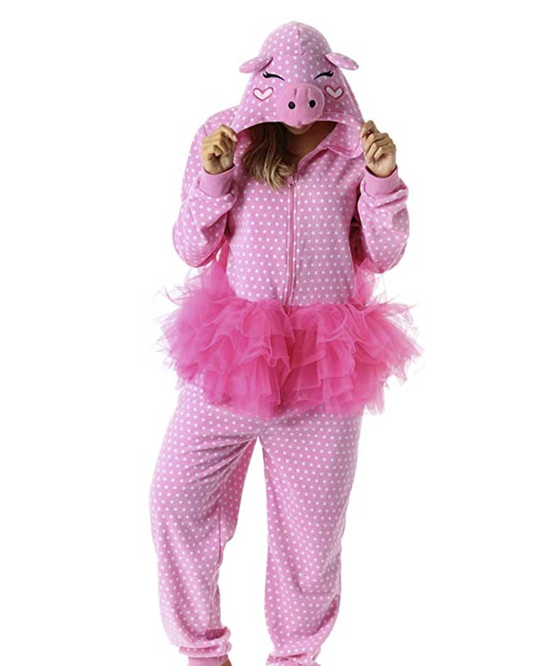 woman in a one piece pajama outfit that is pink with polka dots and an attached tutu. There is a cartoon pig face on the hood of the onesie.